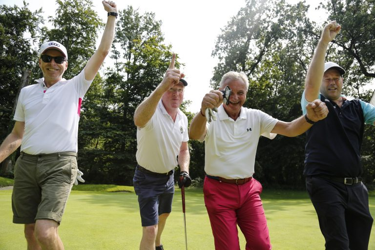 Group of golfers celebrating with arms raised