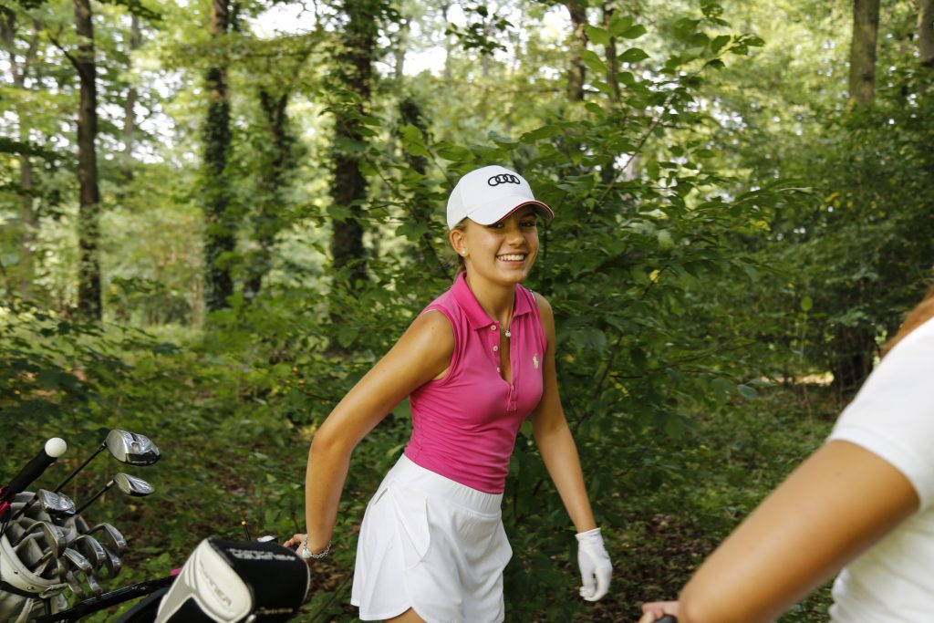 Young woman pulling golf bag trolley smiling