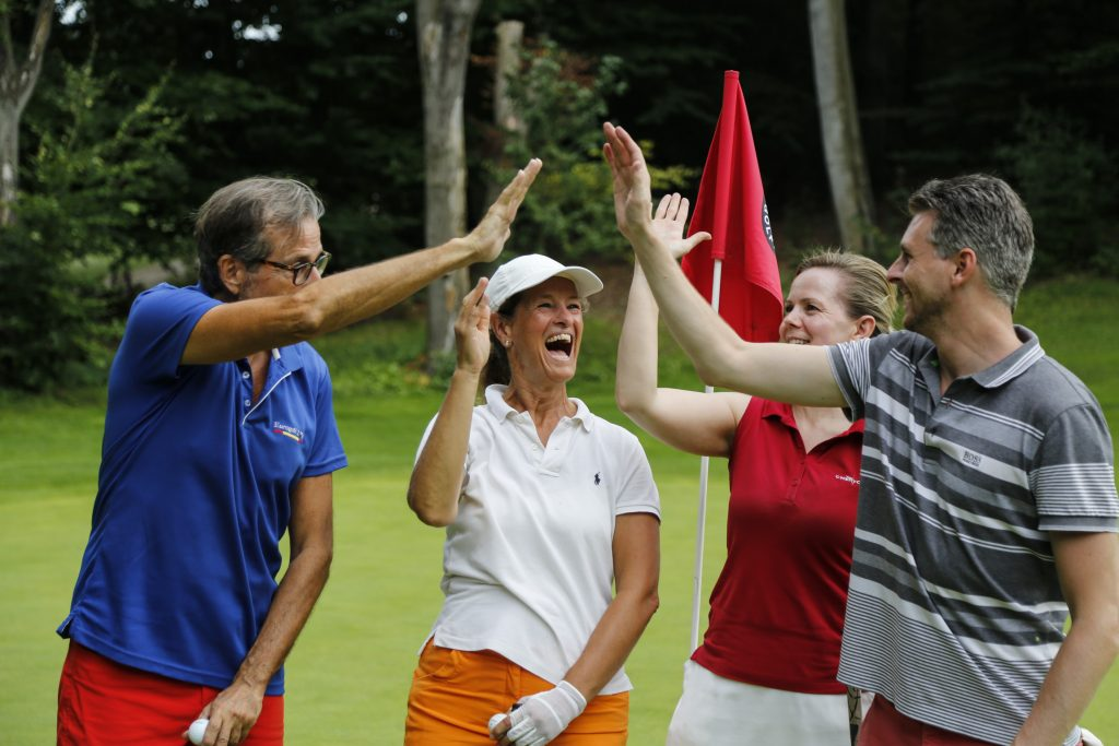 Group of golfers celebrating giving high five