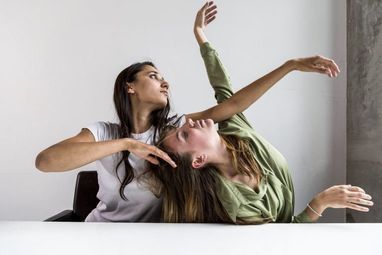 Two young women in abstract pose with arms raised