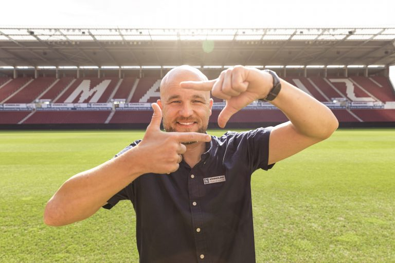 Soccer player posing in stadium with square hand gesture