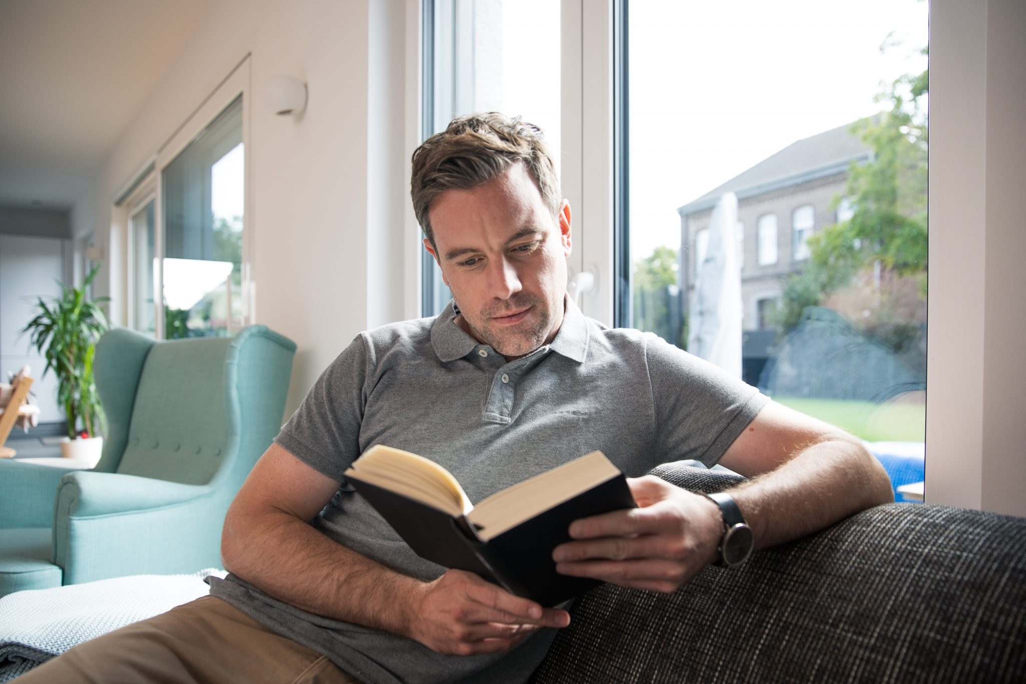 Man reading book on sofa at home