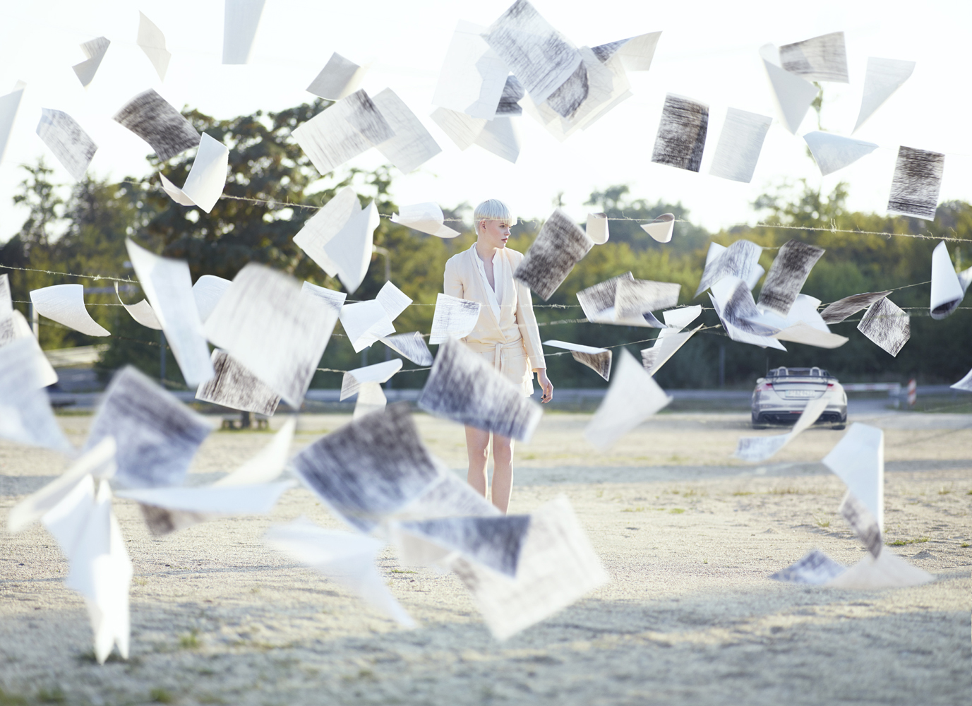 Pages flying outdoors with woman in background