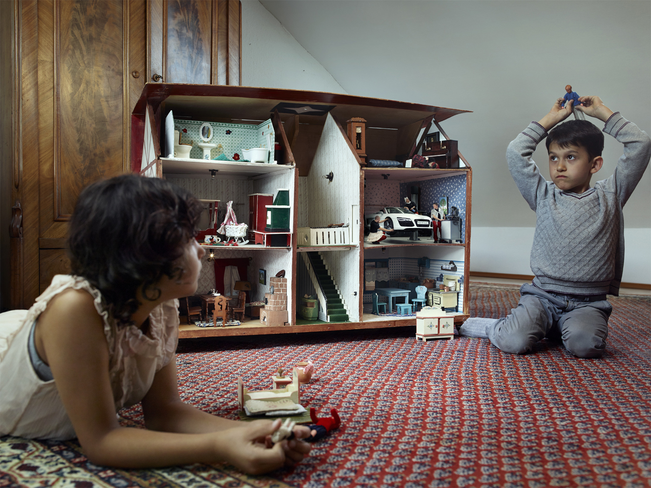 Boy and girl playing with dollhouse